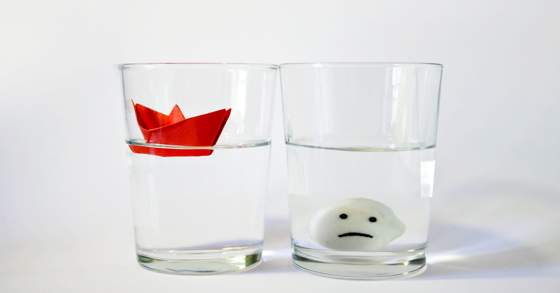 Two glasses of water half full representing two opposite attitudes: optimistic versus pessimistic