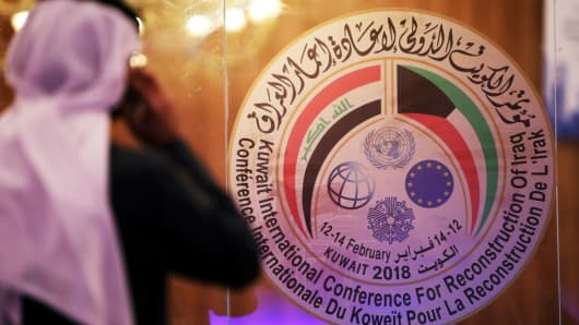 A Kuwaiti journalist speaks on his phone in front of the logo of the Iraq reconstruction conference, at the media centre in Kuwait City on February 11, 2018.