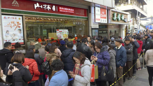 Chinese consumers queue up outside a time-honored grocery store to buy their Chinese New Year essentials in Shanghai.