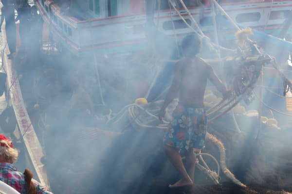 A fisherman in the Gulf of Thailand is engulfed in diesel fumes as his fishing boat comes alongside a navy patrol vessel.