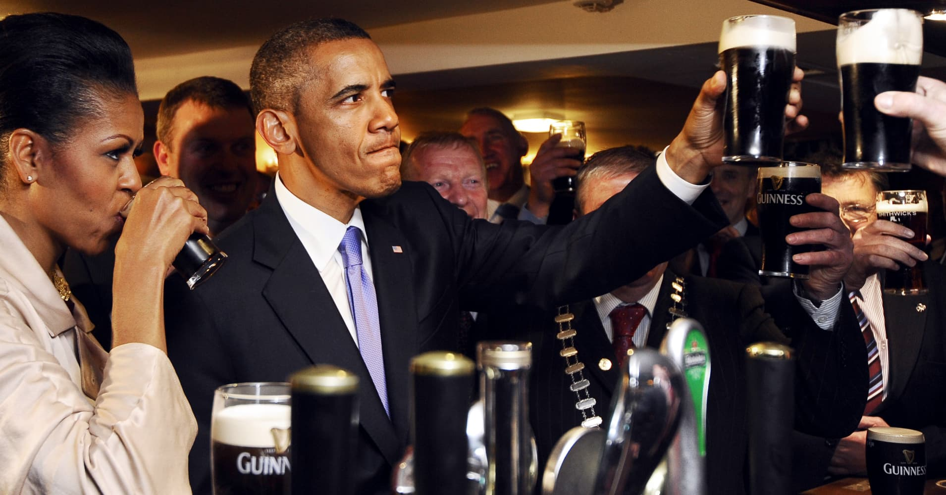U.S. President Barack Obama (2ndL) and First Lady Michelle Obama (L) sip Guinness at a pub as they visit Moneygall village in rural County Offaly, Ireland, where his great-great-great grandfather Falmouth Kearney hailed from, on May 23, 2011.