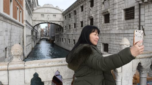 A tourist snaps a selfie with the Bridge of Sighs in the background, on January 19, 2018 in Venice.