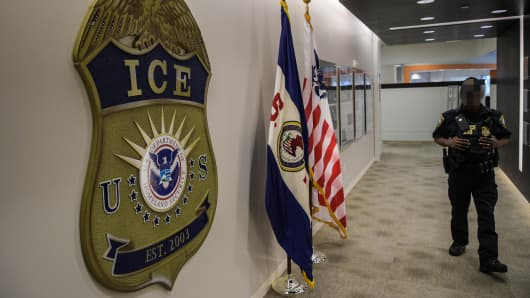 A law enforcement officer walks past ICE logo ahead of a press conference on Thursday, May 11, 2017, at the U.S. Immigration and Customs Enforcement headquarters in Washington, DC.