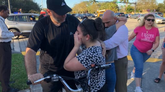 People react after a shooting at Marjory Stoneman Douglas High School in Parkland, Florida.
