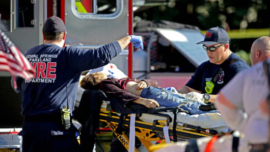 Medical personnel are inclined to a sufferer exterior of Stoneman Douglas Excessive College in Parkland, Florida.