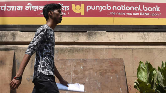 An Indian man walks past a sign for the state-owned Punjab National Bank (PNB) in Mumbai on February 14, 2018.
