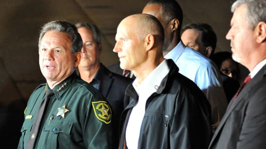 Scott Israel (L), Sheriff of Broward County, and Florida Governor Rick Scott speak to the media as they visit Marjory Stoneman Douglas High School following a shooting that killed 17 people on February 14, 2018 in Parkland, Florida.