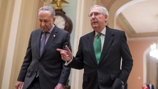 Senate Majority Leader Mitch McConnell, R-Ky., right, and Senate Minority Leader Charles Schumer, D-N.Y., make their way to the Senate floor after announcing a two-year deal on the budget earlier in the day on February 7, 2018.