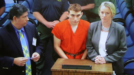 Nikolas Cruz (C) appears via video monitor with Melisa McNeill (R), his public defender, at a bond court hearing after being charged with 17 counts of premeditated murder, in Fort Lauderdale, Florida, U.S., February 15, 2018.
