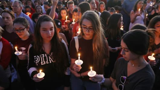 People attend a candlelit memorial service for the victims of the shooting at Marjory Stoneman Douglas High School