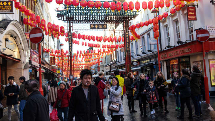 People gather under lanterns in Chinatown on February 15, 2018, in London, England.