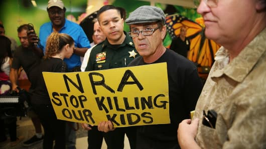A protester holds a sign that reads, 'NRA Stop Killing Our Kids', outside the court-room where Nikolas Cruz, 19, a former student at Marjory Stoneman Douglas High School in Parkland, Florida, was having a bond hearing in front of Broward Judge Kim Mollica at the Broward County Courthouse on February 15, 2018 in Fort Lauderdale, Florida.