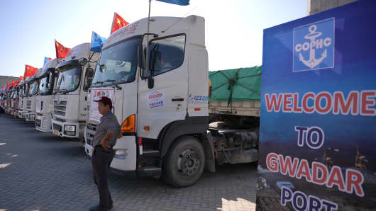 A Chinese worker stands near trucks during the opening of a trade project at Pakistan's Gwadar port on November 13, 2016.