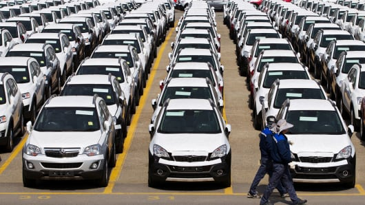 Workers walk past parked General Motors Co. (GM) Chevrolet automobiles bound for export at the Port of Incheon in Incheon, South Korea.