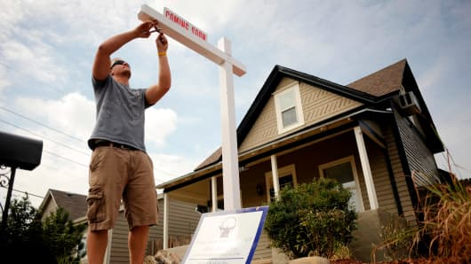Installing a sign for a home for sale in Denver.