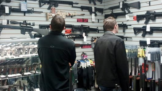 Customers view semi automatic guns on display at a gun shop in Los Angeles, California.