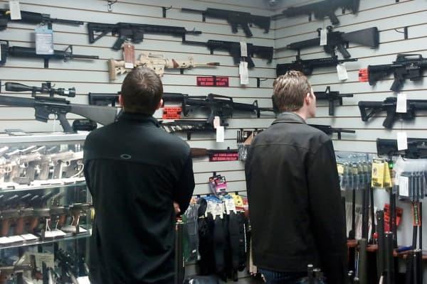 Customers view semi automatic guns on display at a gun shop in Los Angeles, California.