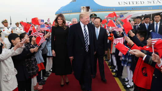 President Donald Trump, greeted by Chinese State Councilor Yang Jiechi (R Center), arrives in Beijing on Nov. 8, 2017, starting his state visit to China.