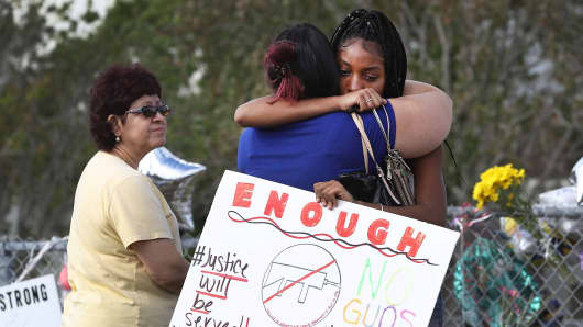 Tyra Heman (R) a senior at Marjory Stoneman Douglas High School, holds a sign that reads, 'Enough No Guns,' as she is hugged in front of the school where 17 people that were killed on February 14, on February 19, 2018 in Parkland, Florida.