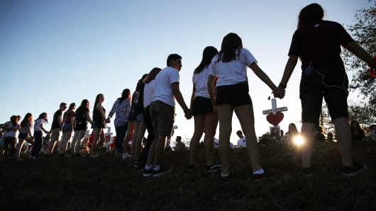 Students and family members holds hands around a makeshift memorial in front of Marjory Stoneman Douglas High School where 17 people were killed on February 14, on February 18, 2018 in Parkland, Florida.