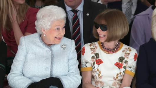 Queen Elizabeth II sits next to Anna Wintour as they view Richard Quinn's runway show before presenting him with the inaugural Queen Elizabeth II Award for British Design.