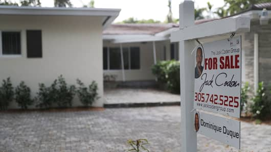 for sale sign is seen in front of a home as the National Association of Realtors released a report showing that home sales dropped in December of 2017 on January 24, 2018 in Miami, Florida.