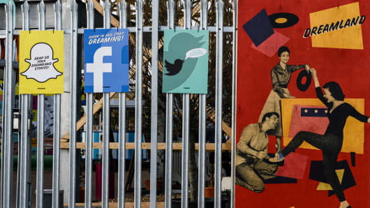 Old style signs next to Snapchat, Facebook and Twitter signs.