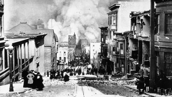 Crumbling buildings line a street and smoke rises in the background after the San Francisco earthquake of 1906.