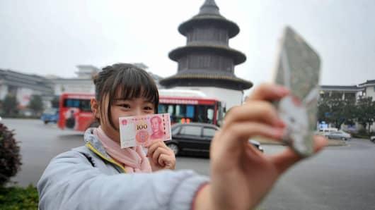 A girl poses with a new 100 yuan note in Yangzhou, Jiangsu Province of China.