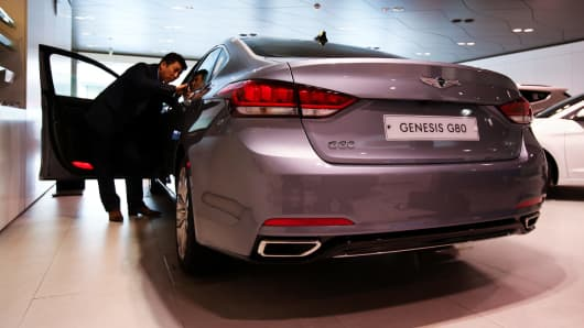 A Hyundai Motor Co. employee inspects a Genesis G80 sedan at a company dealership in Seoul, South Korea.