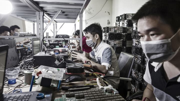 Technicians make repairs to bitcoin mining machines at a mining facility operated by Bitmain in Ordos, Inner Mongolia, China, on Friday, Aug. 11, 2017.