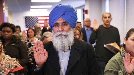 Indian immigrant Darshan Darshan, 64, takes the oath of allegiance to the United States at a naturalization ceremony on January 22, 2018 in Newark, New Jersey.