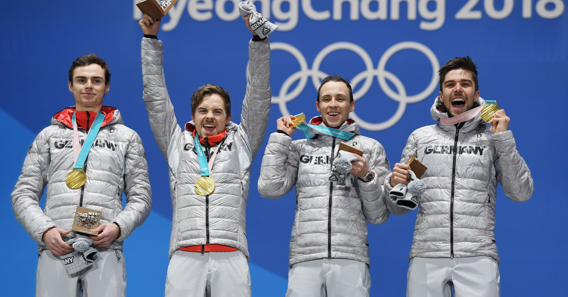 Germany's gold medalists celebrate on the podium during the medal ceremony for the Nordic combined