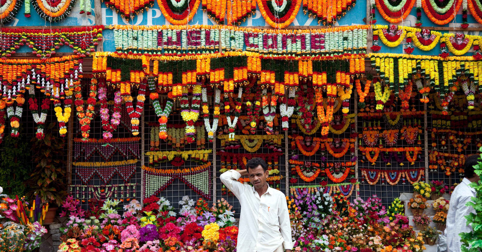 Man tending flower stall on Mutton Street at Chor Bazaar in Mumbai, India