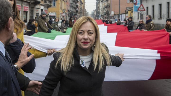 Giorgia Meloni, leader of the right-wing party Fratelli d'Italia (Brothers of Italy) holds a giant Italian national flag during a political rally on February 24, 2018 in Milan, Italy.