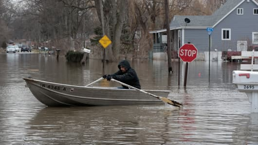 A resident uses a rowboat to navigate a flooded neighborhood on February 22, 2018 in Lake Station, Indiana.