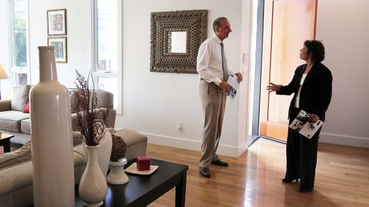 A real estate agent, left, talks with a client during an open house in San Francisco.