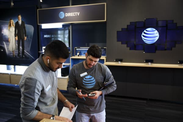 Employees speak at an AT&T Inc. store in Newport Beach, California