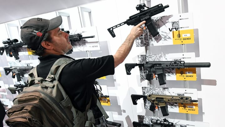 A convention attendee looks at rifles displayed at the Sig Sauer booth at the 2018 National Shooting Sports Foundation's Shooting, Hunting, Outdoor Trade (SHOT) Show at the Sands Expo and Convention Center on Jan. 23, 2018 in Las Vegas.