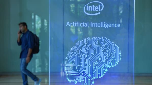 A visitor at Intel's Artificial Intelligence (AI) Day walks past a signboard during the event in Bangalore, India