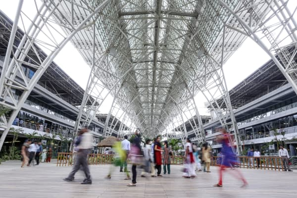 Employees walk through a rest area at the Tata Consultancy Services Ltd. (TCS) campus in the State Industries Promotion Corporation of Tamil Nadu Ltd