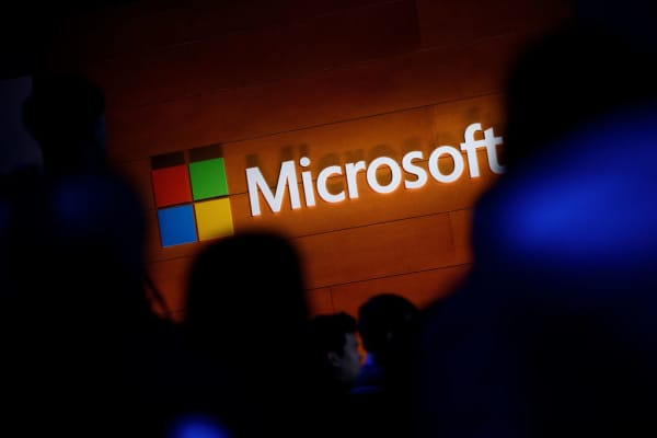 The Microsoft logo is illuminated on a wall during a Microsoft launch event to introduce the new Microsoft Surface laptop