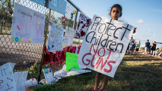 A young school child holds a sign 'Protect Children NOT Guns' at Stoneman Douglas High School.