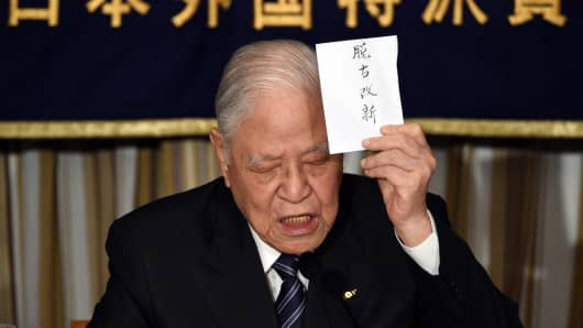 Former Taiwanese president Lee Teng-hui displays a sign reading 'departure from the old, bracing for the new' during a luncheon in which he spoke about the 'establishment of Taiwan's Autonomy' at the Foreign Correspondents' Club in Tokyo, Japan, on July 23, 2015.
