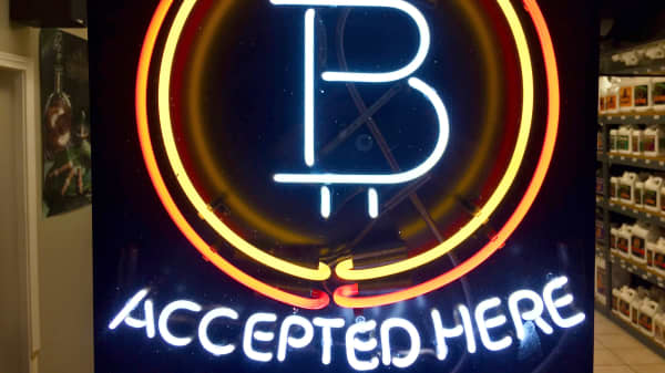 In this Feb. 7, 2018, photo, a neon sign hanging in the window of Healthy Harvest Indoor Gardening in Hillsboro, Ore., shows that the business accepts bitcoin as payment.