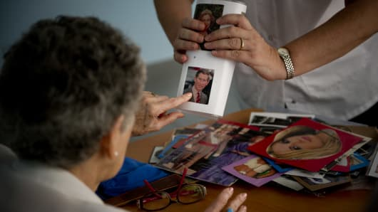 A woman with Alzheimer's performs a memory exercise in a nursing home.