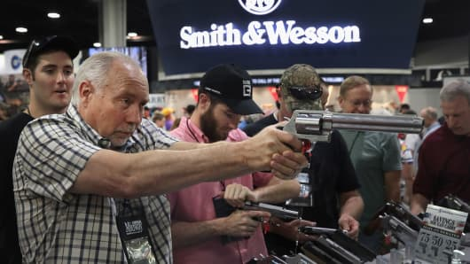 National Rifle Association members look over pistols in the Smith & Wesson display at the 146th NRA Annual Meetings & Exhibits on April 29, 2017 in Atlanta, Georgia.