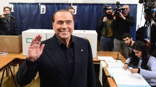 Silvio Berlusconi, leader of right-wing party Forza Italia, waves as he arrives to vote on March 4, 2018 at a polling station in Milan.