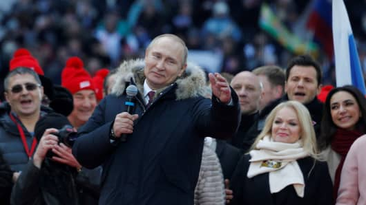 Russia's President Vladimir Putin addresses (C) a rally in his support at the Luzhniki Stadium ahead of the 2018 Russian presidential election scheduled for March 18, in Moscow, Russia on March 03, 2018.