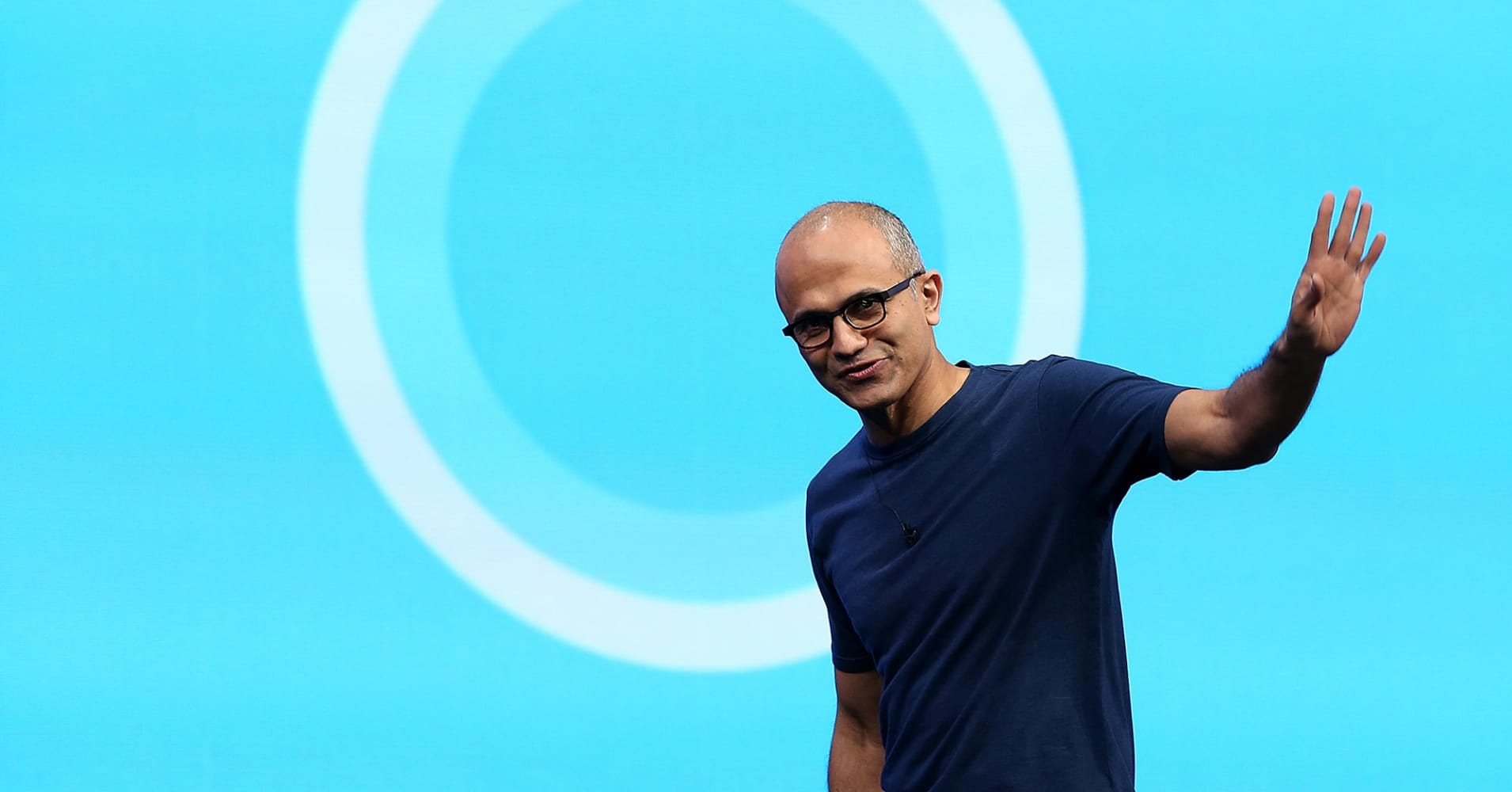 Microsoft CEO Satya Nadella walks in front of the Cortana logo.